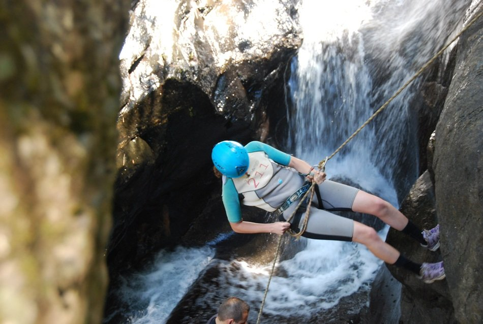 rock climber over a waterfall