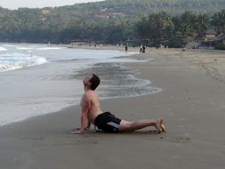 Man on the beach in yoga pose