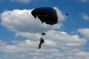The paratrooper is hovering against the cloudy sky