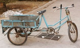 old weathered cargo bike on pavement