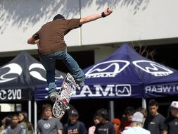 skateboarder in jump above crowd