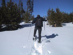 man goes snowshoeing in the snow