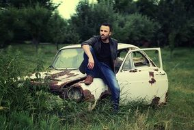 a man posing on an old rusty car
