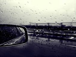 Black and white photo of car in the rain