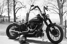 black and white photo of harley davidson next to the helmet