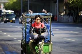asian man riding truck on street, china, beijing