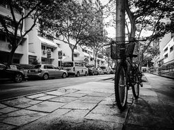 black and white photo of a bike is parked on the street
