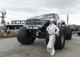 cowgirl posing in front of monster truck on exhibition, usa, texas