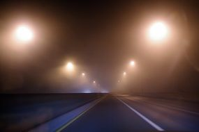 street lights above road at mist