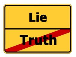 "Yellow street sign ""lie"" and crossed out ""truth"""