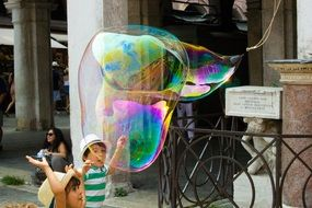 children playing with soap bubbles on the street