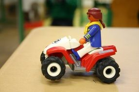 girl riding playmobil, toy on table