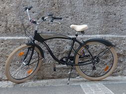 black vintage bike by the stone wall