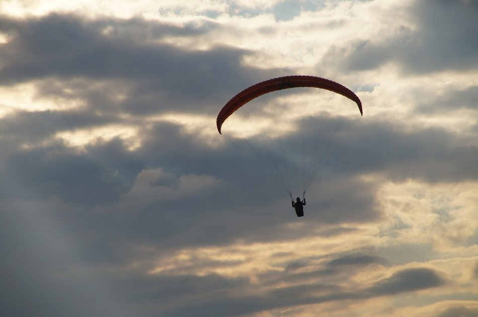 paraglider at cloudy evening sky