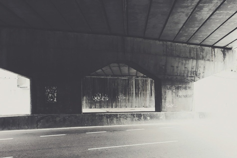 overpass road with graffiti black and white scene