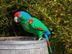 A parrot on a barrel made of colorful Lego blocks