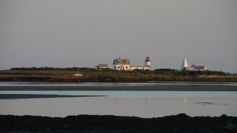 old light house on island at sunset