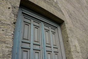 weathered blue wooden door in aged grey stone wall