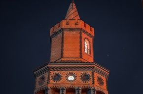 top of brick tower with illuminated windows at night sky