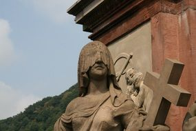 statue of a girl with her eyes closed and the cross of the heidelberg bridge