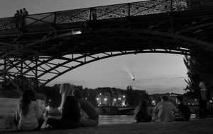 people on the river bank under the bridge in paris