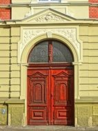 red wooden entrance door in old stone facade, poland, bydgoszcz