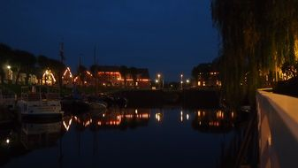 town on coast of north sea at night, germany, east frisia, caroline harbour