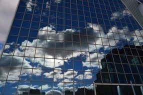 Reflection of clouds in the glass facade of the building