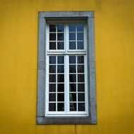 grated window in yellow facade