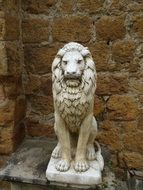 lion, aged marble sculpture at stone wall