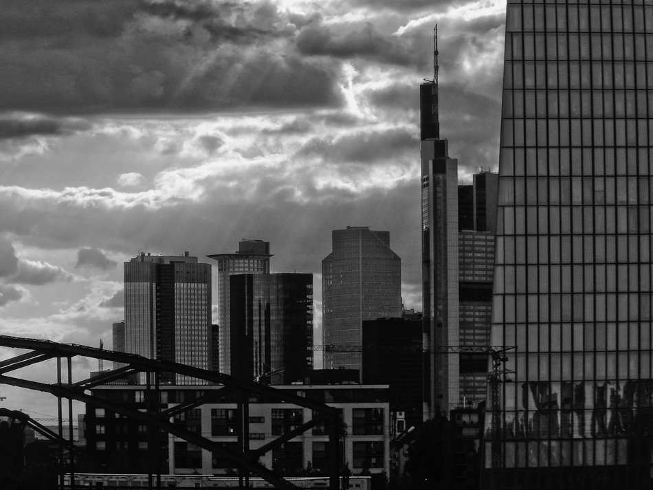 black and white photo of skyscrapers, bridge and clouds