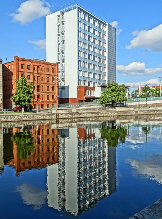 buildings are reflected in water in bydgoszcz
