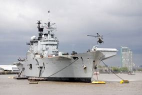 helicopter above aircraft carrier lying at anchors on thames river, uk