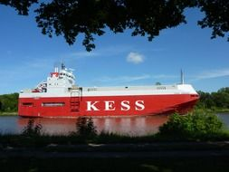 "red ship with the name ""Kess"" on the river"