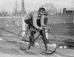 Black and white old photo of men cycling in races