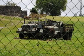 two old military trucks on the fence