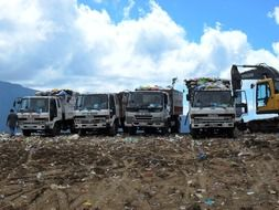 trucks with garbage at the dump