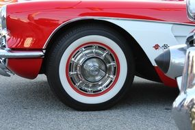 side of vintage car with red and white tire