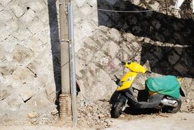 yellow scooter is parked against a stone wall