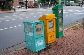 three newspaper boxes