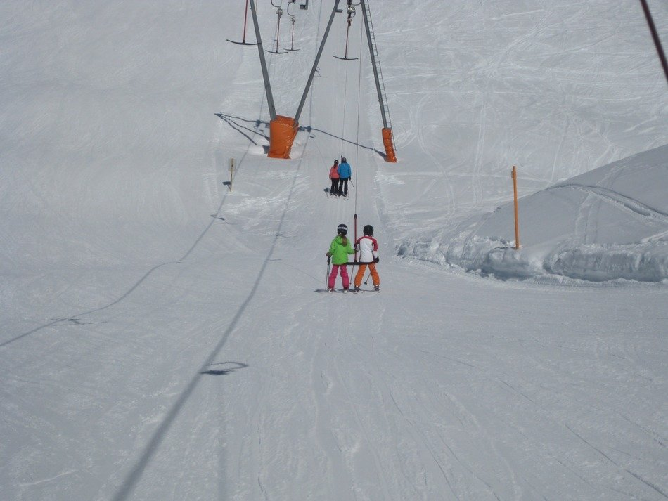 people on the ski lift on a sunny day