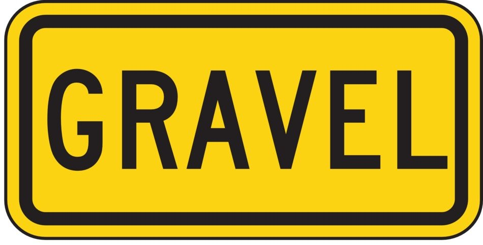 yellow road sign warning about gravel