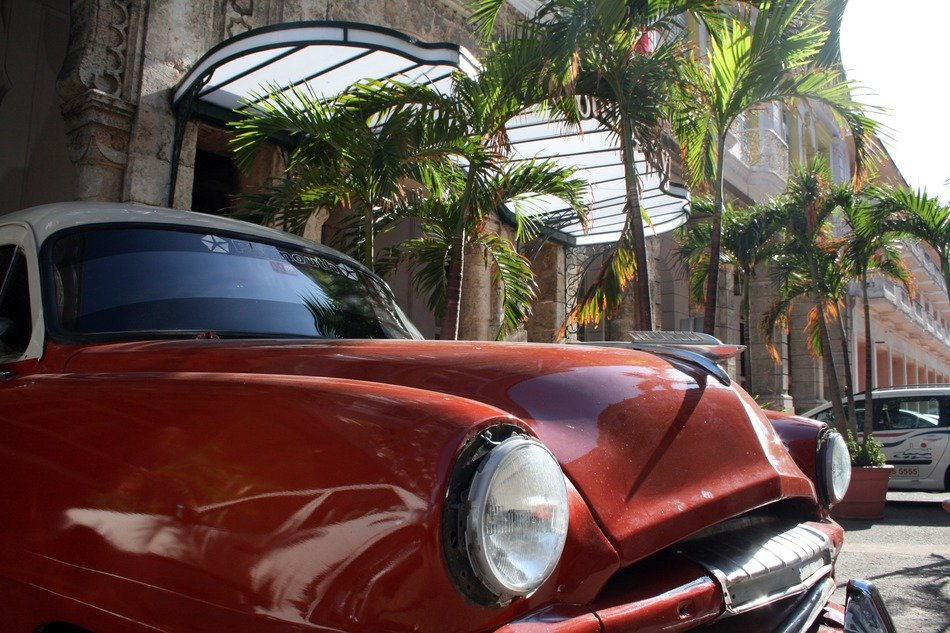 front of red oldtimer car, cuba