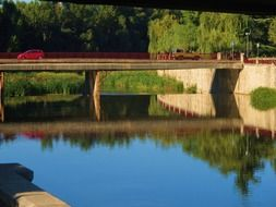 automobile bridge is reflected in the river among picturesque nature