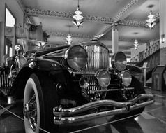 black and white photo of an antique car in a museum