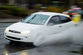 white car in aquaplaning on the road
