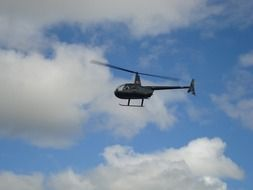 hovering helicopter in sky beneath clouds