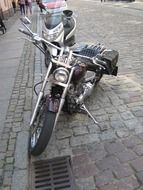 motorcycle stands on cobblestone pavement at roadside