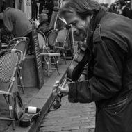 black and white photo of a street musician in paris with a guitar