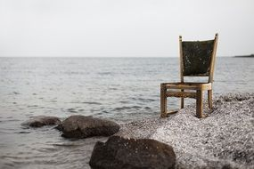 armchair stands on the beach near the water